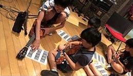 スタジオで子どもたちにウクレレ指導。「きょうの出来栄えは90点でした!」