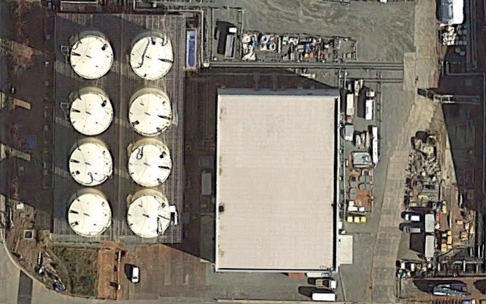 中央の建物がサブドレン他浄化設備。左のタンクが1基1000トン容量の一時貯水タンク(左上から下にA、B、C、D…の順で右下の1基は別用途:RO濃縮水処理設備)(Google Mapに加筆)