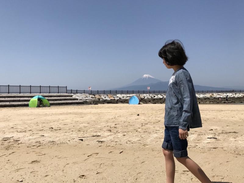 裸足で砂浜の感触を確かめる娘。ビーチに「ダイナマイト・キッドみたいなすごいマッチョの白人男性」と「たいめいけんのシェフのように日焼けした日本人男性」がいたので目を白黒させていました。