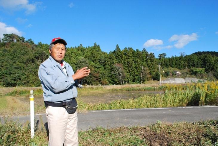 いわき市小久地区の田んぼで、放射能に負けないコメ作りについて語る佐藤三栄さん