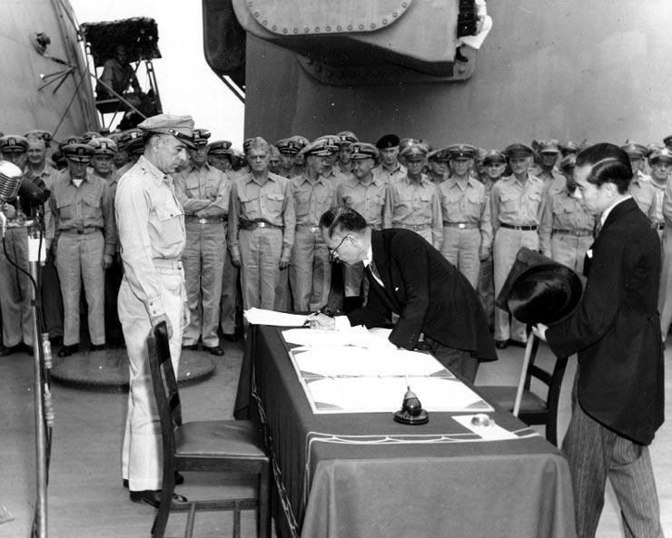 キャプションを原典から直訳「1945年9月2日、戦艦ミズーリの艦上で降伏文書にサインする重光葵外務大臣。左はマッカーサーの副官であるリチャード・K・サザーランド大将。外務省の加瀬俊一が重光外相をサポートしている」Naval Historical Center Photo
