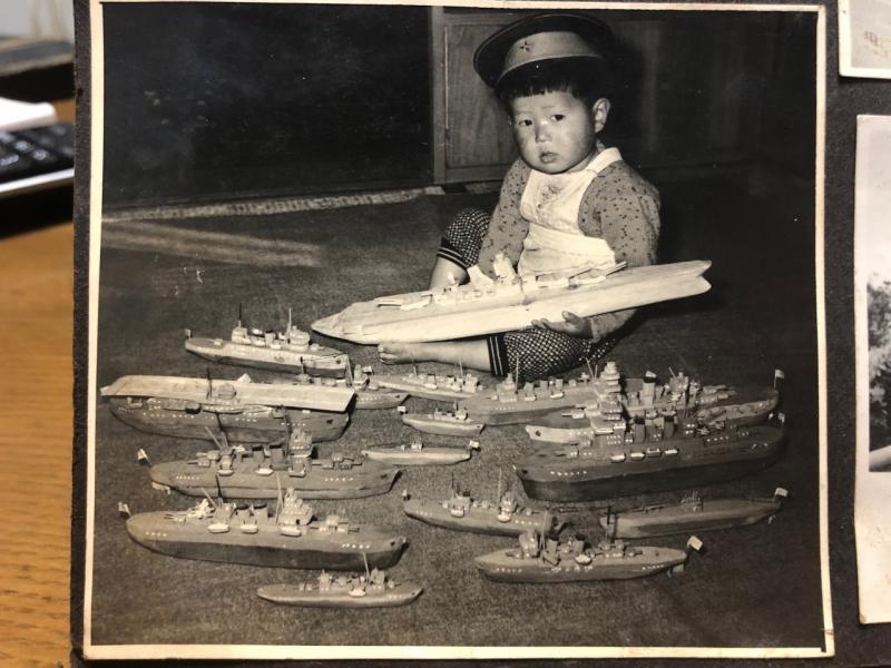 祖父が木材を削って作った軍艦と一緒に写る父