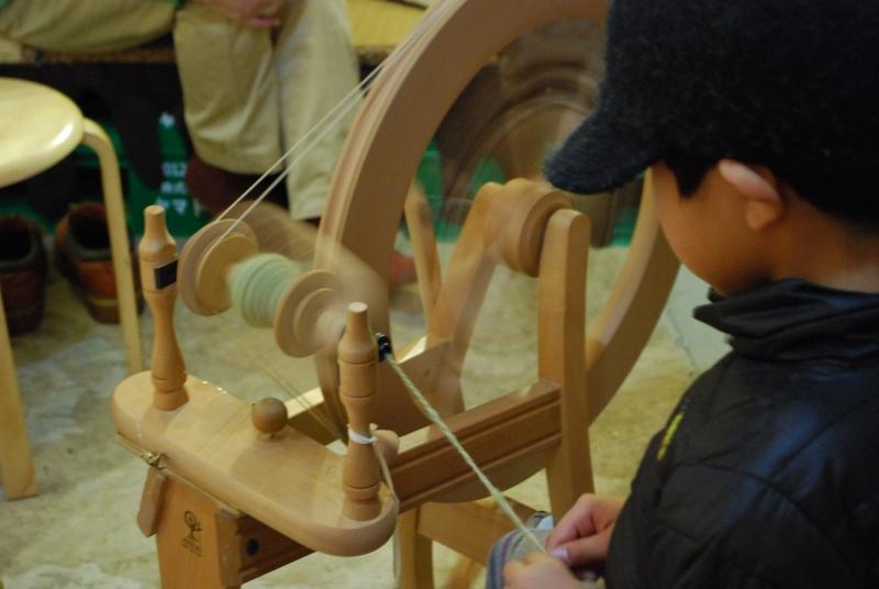 カーダーで繊維を揃えた羊毛を糸車で糸につむいでいく。けっこうコツが必要なんだけど、アートセンターの常連、小学5年生くんが大活躍