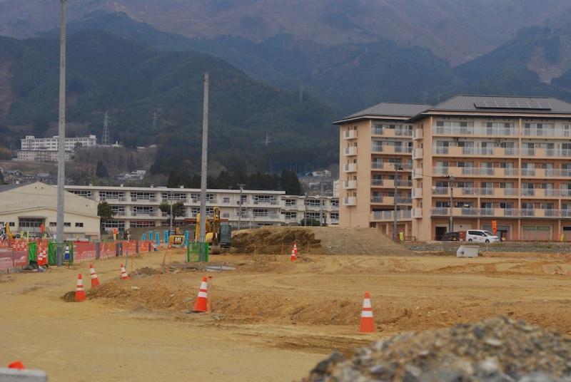 奥の白い建物が新市庁舎建設予定地の高田小学校。手前は2014年完成の災害公営住宅