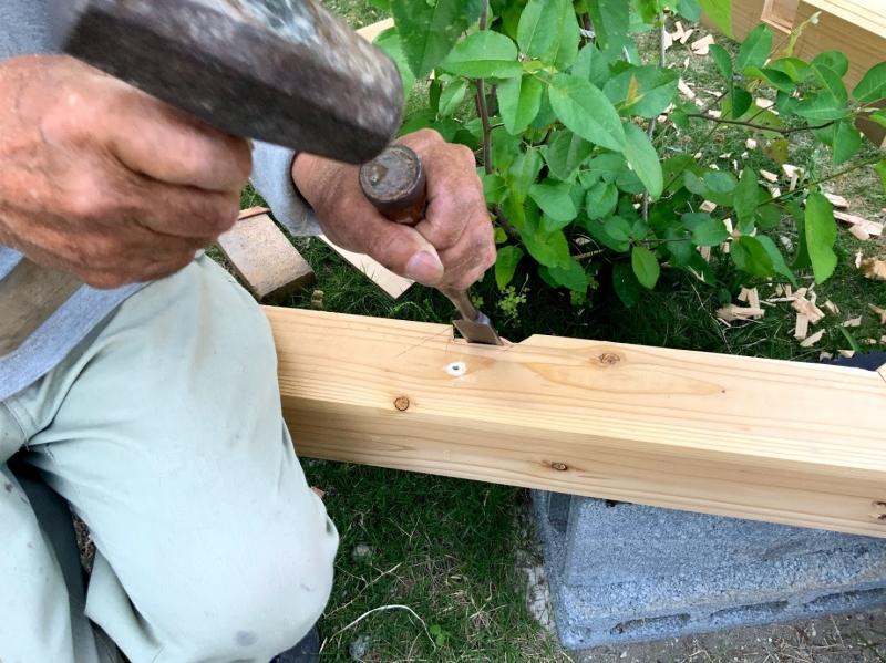 鑿(ノミ)で根太を張るために、大引き(おおびき)を削って溝を作成する義父。