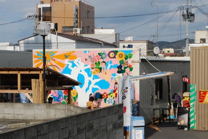 花の芽をつなぐ運動・第一弾。多摩美術大学の学生有志が描いた壁画を商店街の南側から