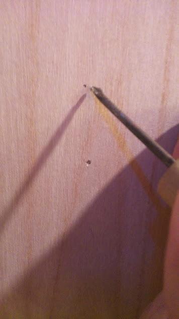 目印を付けた場所に、千枚通しで軽く穴を空けておきます。こうすることで、ネジを正確な位置に打ち込むことができるのです!(すぐ下の穴は間違えて空けてしまったようです・・・)。