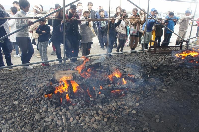 石を熱する焚火、珍しいこともあってか観衆もこんなに