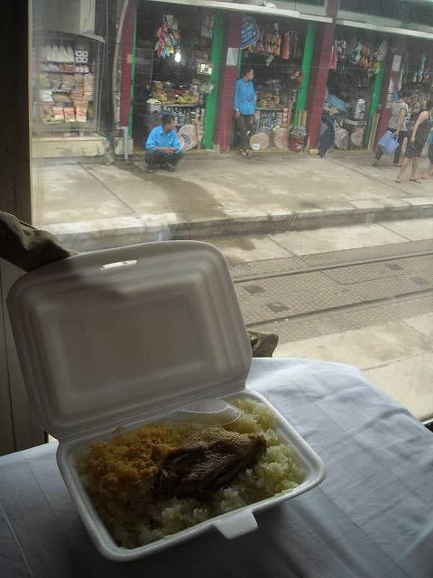 購入したお弁当。車窓に見えるのはお弁当を買ったホーム脇にあるお店