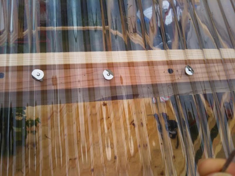 屋根にクリアポリカを貼っているところ。釘の傘部分が波の形状にピッタリ合い、スポンジが雨水の侵入とポリカに傷がつくのを防ぎます。