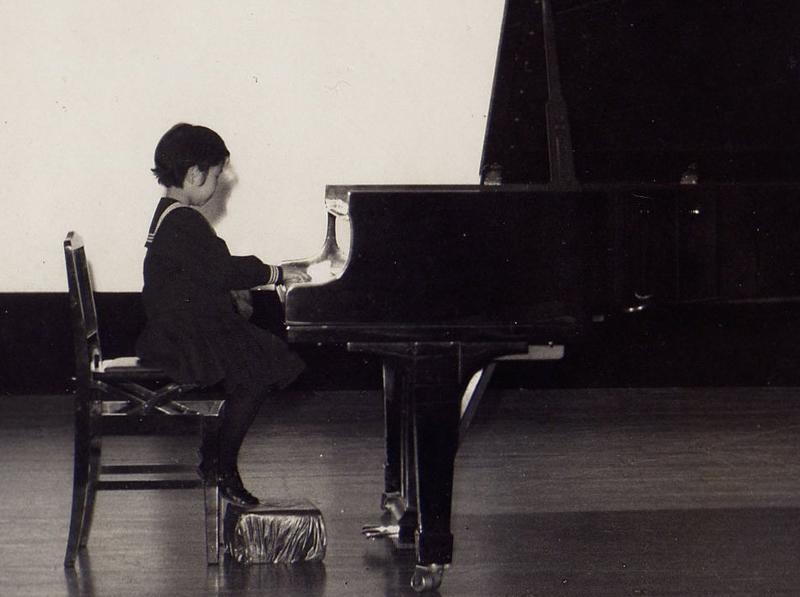 学習院の制服を着てピアノの発表会。イスに座ると足が届かないほど小さかった。