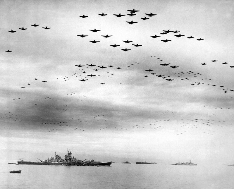 キャプションを原典から直訳「1945年9月2日、日本の降伏:海軍の艦載機が降伏式典の間、米英艦隊の上空を編隊飛行した。左は戦艦ミズーリ、右は軽巡洋艦デトロイト。航空機はグラマンTBMアベンジャー雷撃機、グラマンF6F戦闘機、カーチスSB2Cヘルダイバー爆撃機、チャンスボートF4U戦闘機など」