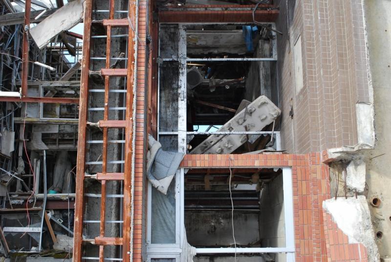玄関の中には外壁パネルに抱きつくような形でテーブルが残されていた。布団やカーテンも窓枠に絡みついたまま(2013年1月)