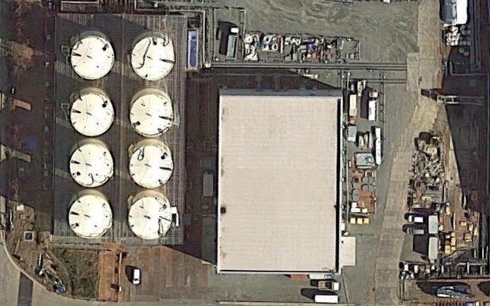 中央の建物がサブドレン他浄化設備。左のタンクが1基1000トン容量の一時貯水タンク(左上から下にA、B、C、D…の順で右下の1基は別用途:RO濃縮水処理設備)(Google Mapより)