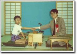 90年頃の羽生善治棋士と握手をする竜王は7~8才で、歳の差15才程