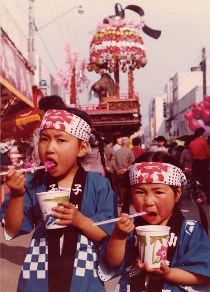 春祭りにて、愛香さん4歳、姉7歳。太鼓を叩いた後、ご褒美のかき氷を頬張る姉妹。