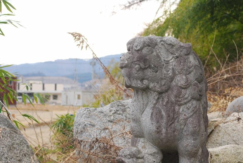 あの日多くの人たちが避難した本丸公園への登り口に置かれたままの被災した狛犬