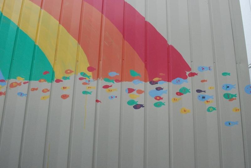 虹の続きが描かれた仮設店舗の外壁にはかくれキャラ。