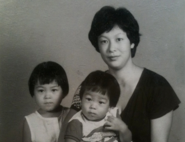 1才頃、母に抱かれて記念写真。傍らは2歳違いの姉。