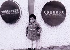4歳頃の薫堂さん。白いタイツとムクムクのピーコートというファッションがお坊ちゃま風。